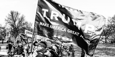 Trump supporters hold a flag stating 'Trump: Make America Great Again'.